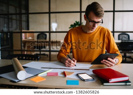 Concentrated creative architect holding modern tablet in hand and drawing sketch of building on paper sitting at desktop with equipment and tube in studio.Pensive hipster guy writing note on blueprint