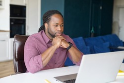 Concentrated dark skinned guy looking for issues solving, African-American businessman sitting at the desk and staring thoughtfully at the laptop screen, reading and analyzing technical task