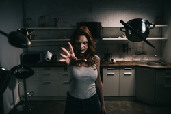 concentrated demoniacal girl with levitating kitchenware in kitchen
