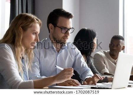 Concentrated diverse colleagues sit at desk brainstorm work on laptop together, focused multiracial businesspeople cooperate discuss ideas using computer at office meeting, collaboration concept