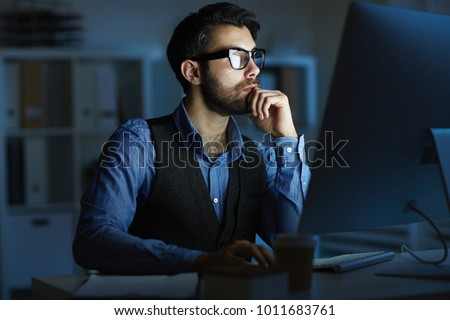 Concentrated entrepreneur or manager sitting by desk in front of computer monitor while working at night