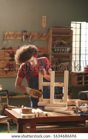 Concentrated female carpenter in earmuffs and protective gloves carefully polishing wooden stool lying upturned on table