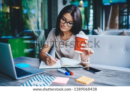 Concentrated female student writing in notebook while learning with cardboard coffee cup in cafe, pensive woman freelancer noting information for planning project doing remote job via laptop computer