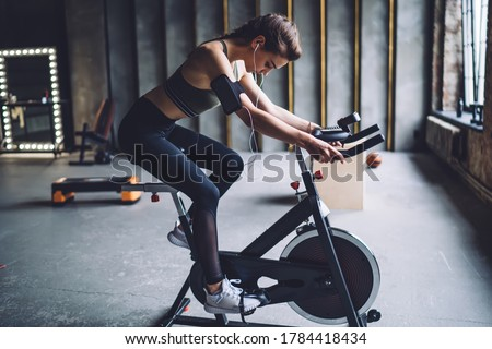 Concentrated fit female in sportswear with dark braided hair burning calories on spin bike and listening to music in headphones
