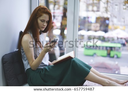 Concentrated foxy hipster girl reading messages in chat on modern smartphone connecting to high speed 4G internet sitting on windowsill with bestseller book.Advertising area for your text message #657759487