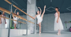 Concentrated girl ballerina does exercise with raised in splits leg leaning on barre under teacher control in studio