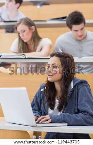 Concentrated girl sitting at the lecture hall with her laptop
