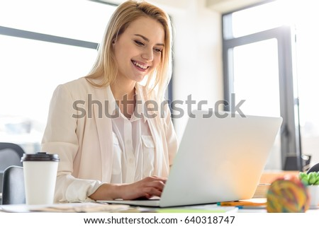 Concentrated gorgeous girl smiling while typing on computer #640318747
