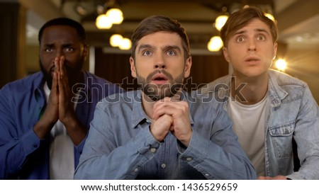 Concentrated guys watching game, worrying about match results, waiting for goal