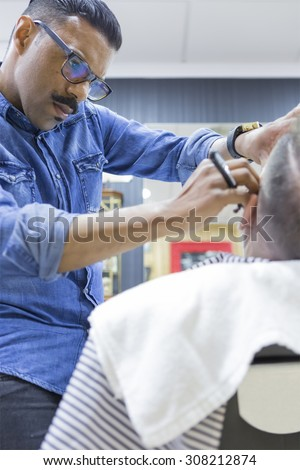 concentrated hairstylist is shaving a beard of a customer in a barber shop - focus on the face