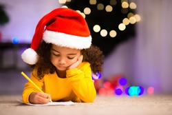 Concentrated little afro girl writing letter to Santa Claus, lying on floor near Christmas tree, free space