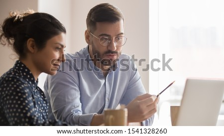 Concentrated male businessman looking at computer monitor, working with a young Indian female worker on a project, people holding a video meeting with a client or interviewing a job candidate.