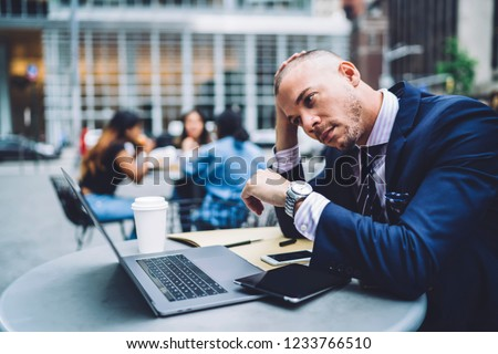 Concentrated male entrepreneur worried about financial report on laptop during coffee break in downtown cafe, thoughtful businessman reading and analyzing information from online exchange on web page
