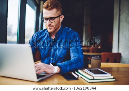 Concentrated male freelancer searching information for creating and programming new website for company order, serious hipster guy in optical eyeglasses reading news about internet provider via laptop