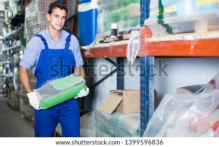 concentrated male in uniform is choosing cement in the building store room