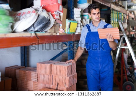 concentrated male in uniform is choosing tile in the building store room