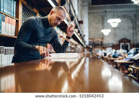 Concentrated male journalist analyzing content of book making research for writing article, clever academic professor learning in university library increasing knowledge in nonfiction literature