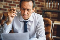 Concentrated male person looking at papers