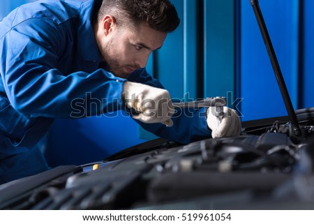 Concentrated mechanic repairing car engine