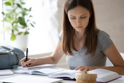 Concentrated millennial girl sit at desk at home studying using textbooks handwriting in notebook, focused smart female student prepare homework, get ready for exam or test, education concept