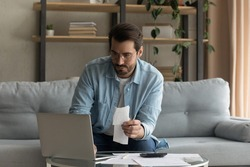 Concentrated millennial man look at laptop paying bills or taxes online on gadget. Focused young Caucasian male manage household finances expenditures, take care of family budget using computer.