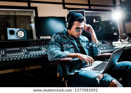 concentrated mixed race sound producer in headphones using laptop in recording studio
