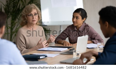 Concentrated multiethnic businesspeople gather at desk in office discuss business ideas together, focused diverse multiracial colleagues brainstorm consider project at meeting, cooperation concept