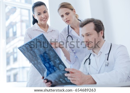 Concentrated neurologist examining brain x ray image indoors
