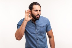 Concentrated nosy man with beard in blue shirt holding hand near ear, listening to interesting talks and private secrets, spying. Indoor studio shot isolated on white background