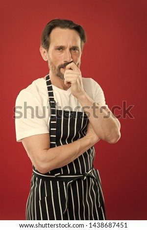 Concentrated on the task. Doing household. Bearded mature man in striped apron. Senior cook wearing bib apron. Mature person in cooking apron. Aged master of the household. Home cooking. #1438687451