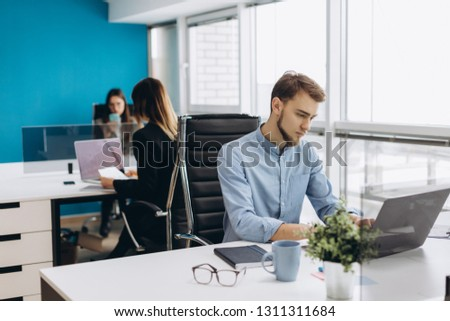 Concentrated on work. Concentrated young beard man working on laptop while sitting at his working place in office