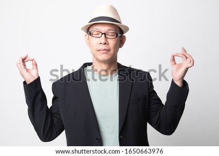 Concentrated relaxed   adult asian man  closed eyes, having relaxation while meditating, trying to find balance and harmony Yoga and meditation concept on white background