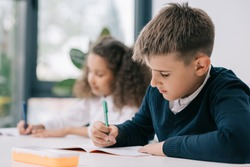 Concentrated schoolboy sitting at desk and writing in exercise book with classmate sitting behind