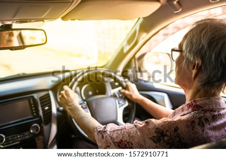 Concentrated senior woman driver hold steering wheel steady using slow speed to avoid accidents,asian elderly people driving careful,concentrating while driving car in city,traffic,road safety concept