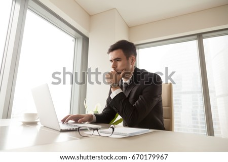 Concentrated serious businessman using laptop computer, working online, looking at screen, managing new project, trying to solve problem, analyzing market, running e-business, browsing internet on pc