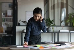 Concentrated serious young indian female employee managing working tasks with colorful stickers or preparing presentation, holding mobile phone call with boss or consulting client distantly in office.