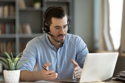 Concentrated skilled millennial caucasian businessman in glasses wearing headphones with mic, taking part in online web camera negotiations meeting using computer app, distant communication concept.