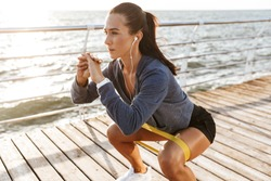 Concentrated sportswoman doing exercises with a rubber band at the beach