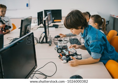 concentrated teen child constructing robot at class, stem education concept