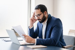 Concentrated tired stressed depressed serious arabian businessman having problems at workplace, solving job issues, doing paperwork. Deadline, paying bills, debt and loan concept. Headache migraine