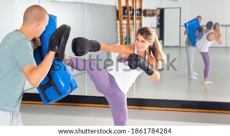 Concentrated woman practicing self-defense techniques in gym, kicking boxing shield in hands of her coach Stock fotó ©