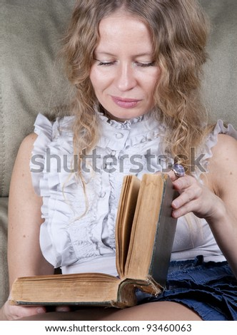 Concentrated  woman reading a book at home in the living-room