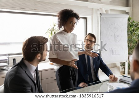 Concentrated young african ethnicity businesswoman in formal wear standing at table, reporting working issues to focused male colleagues at briefing meeting indoors, providing professional assessment.