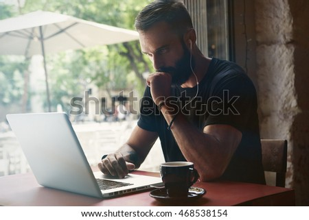 Concentrated Young Bearded Businessman Wearing Black Tshirt Working Laptop Urban Cafe.Man Sitting Wood Table Cup Coffee Looking Through Window.Coworking Process Business Startup.Blurred Background. #468538154