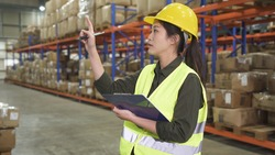 concentrated young beautiful asian korean lady worker pointing finger and counting parcels on clipboard in large stockroom.