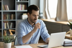 Concentrated young businessman in eyewear looking at laptop screen, web surfing information in internet or working distantly online at home office, communication remotely with client or study.