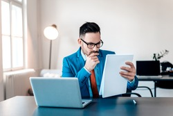 Concentrated young businessman reading documents at office desk.