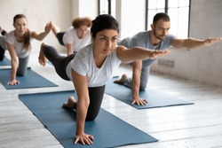 Concentrated young female indian trainer showing bird dog pose at group yoga class. Fit barefoot diverse people practicing body balancing exercise in Parsva Balasana position on mat indoors in gym.