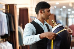 Concentrated young Indian tailor measuring bespoke jacket shoulders with tape measure