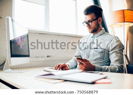 Concentrated young IT developer checking mail on smartphone while working in office on computer, skilled male programmer in eyeglasses synchronizing multimedia files from mobile phone in application